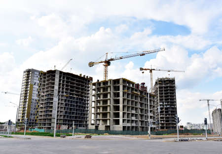 Tower cranes in action at construction site. Construction process of the new modern residential buildings. Road work and streets repair in city. Preparing to pour of concrete into formwork.