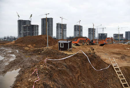 View of a large construction site. Excavator for earthworks. Tower cranes are building multi-storey residential buildings. Фото со стока