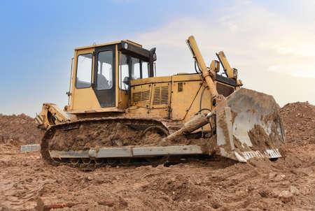 Dozer on earthmoving at construction site on sunset background. Construction machinery and equipment on groundwork. Bulldozer leveling ground for new road construction. Фото со стока