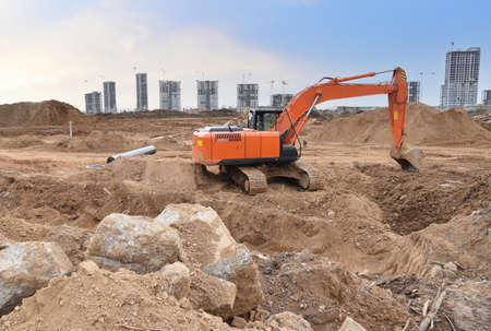 Excavator on earthworks at construction site. Backhoe on earthmoving and foundation work. Heavy machinery and equipment. Фото со стока