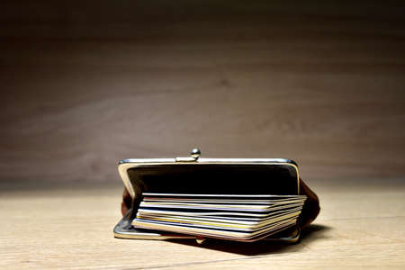 Plastic bank cards in retro wallet on wooden background