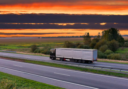 Trucks with Semi-trailer driving on highway on sunset background. Goods Delivery. Services and Transport logistics.
