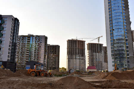 View of a large construction site with buildings under construction and multi-storey residential homes. Tower cranes in action on blue sky background. Housing renovation concept. Crane during formworks