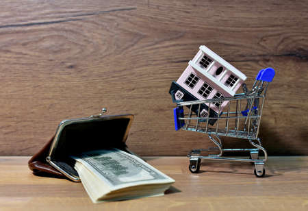 House in Supermarket Trolley and purse with american dollars. Home buying or selling. Credit housing or renting an apartment. Miniature Home for family with Hundred Dollar Bills. Real Estate Investing Фото со стока