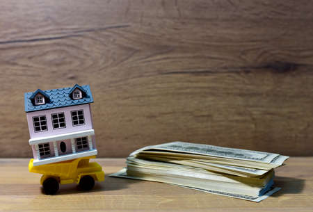 Miniature dump truck delivers a miniature family home at american dollars. Building on credit housing or renting an apartment. Home with Hundred Dollar Bills. Real Estate Investing and Housing Market