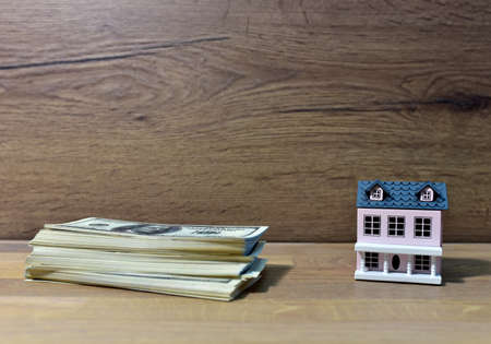 House and american dollars. Home buying or selling. Building on credit housing or renting an apartment. Miniature Home for family with Hundred Dollar Bills. Real Estate Investing and Housing Market