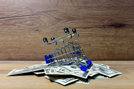 Supermarket basket lies on a heap with American dollars. Shopping cart trolley at Hundred Dollar Bills. Lots of money for shopping. The cost of food and clothing in the store. Social problem