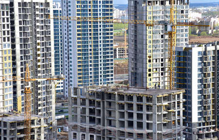 Tower crane during construction of a residential building. Cranes on formworks. Construction the building or multi-storey homes, Arial view. Renovation concept. Realtor and Real Estate