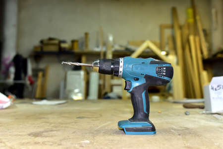 Cordless combi drill for used as impact drill and screw driver. Cordless impact screwdriver for work with self-tapping screws. Brushless battery drill on a wooden workbench in furniture workshop