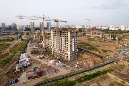 Crane during formworks. Aerial View of a large construction site. Tower cranes in action. Housing renovation concept. Construction the buildings and multi-storey residential homes Stock Photo
