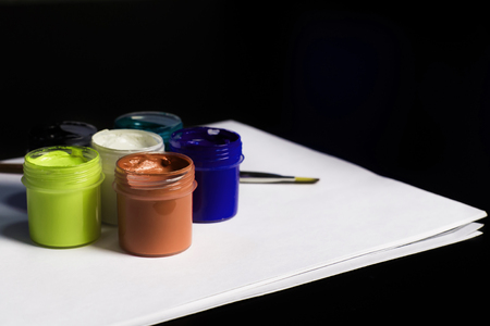 Multicolored cans of gouache with Paintbrush