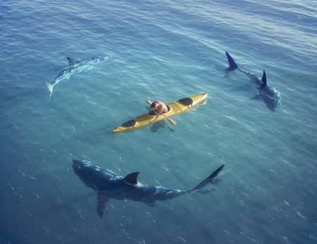 A man in a boat, kayak  was trapped in the middle of the ocean surrounded by sharks