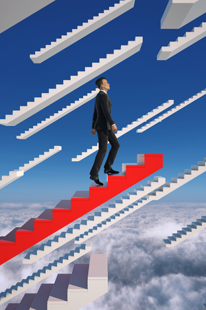 Go to success. Businessman climbs a red flying stairs.