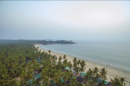 Aerial view of the beautiful coastline of the Indian Ocean with tropical forest, sandy beach, calm blue water and fishing boats in Goa, Palolem beach Banco de Imagens