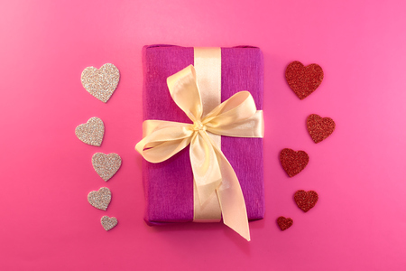 Present or gift box, paper heart and confetti on pink background top view. Valentines day greeting card. Flat lay style.