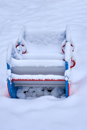 Close up of a snow covered blue boat shaped seesaw teeter totter in a children play park during the cold winter season.
