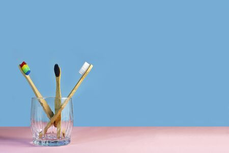 Bamboo toothbrushes in glass on a colored blue and pink background. Biodegradable bamboo toothbrush, environmentally friendly. Dental care concept. Copy space for text.