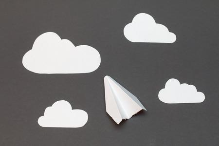 nubes caricatura: Avión de papel blanco con las nubes en un fondo gris