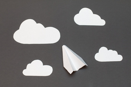 clouds cartoon: White paper airplane with clouds on a gray background