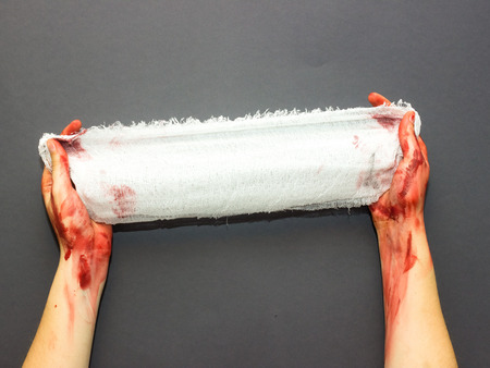bloodied womans hands holding a bandage stained with blood on a gray background to the theme of Halloween