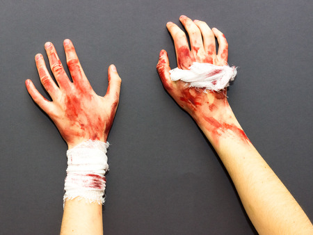 bloodied female hands tied with a bandage stained with blood on a gray background to the theme of Halloween