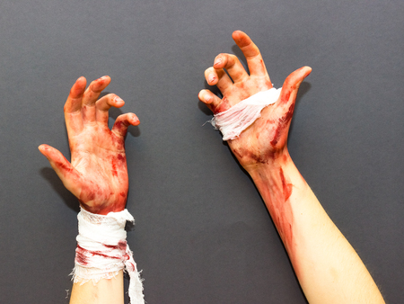 bloodied: bloodied female hands tied with a bandage stained with blood on a gray background to the theme of Halloween