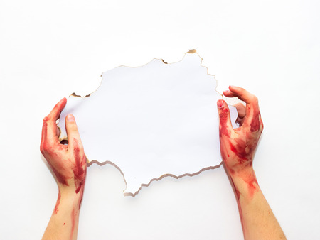 bloodied: bloodied womans hands holding an old white sheet on a white background to the topic of Halloween