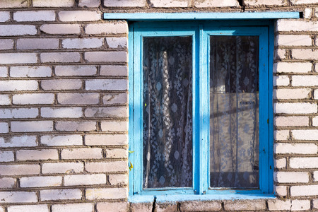 panes: blue old wooden window in the house from a white brick village