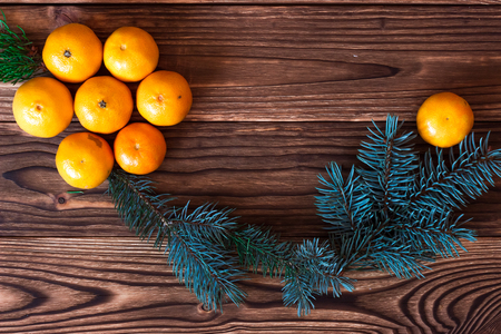 next year: Christmas and New Year Mandarins next to the Christmas tree branches with cones on a wooden background