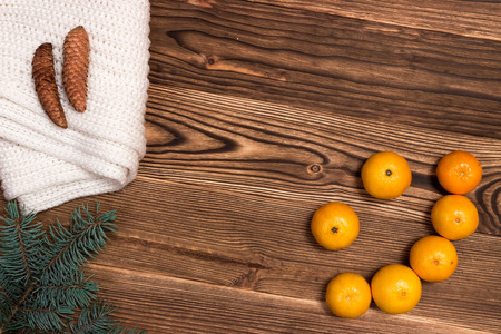 next year: Christmas and New Year Mandarins in the form of a smile, next to the Christmas tree branches with cones on a wooden background Stock Photo