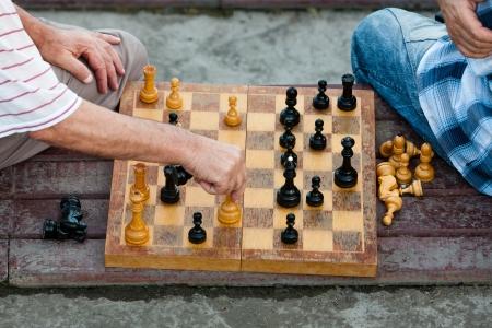 dos viejos juegan al ajedrez de edad en un tablero de ajedrez experimentado Foto de archivo
