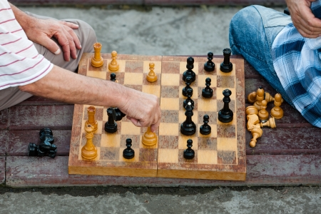 two old men play old chess on a seasoned chess board Stock Photo