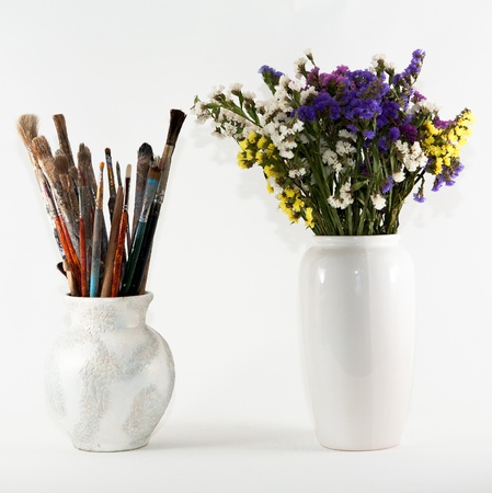 jug with paint brushes and vase with wild flowers Stock Photo