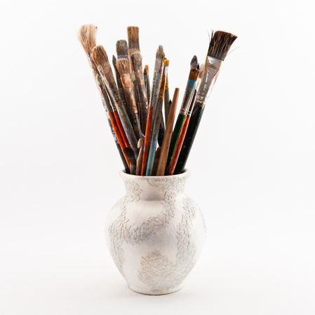 jug with paint brushes on the wight background