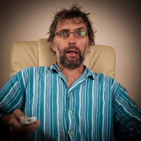 hombre necio mira espect�culo terrible en TV Foto de archivo