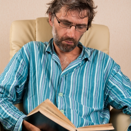 mature man sitting in chair reading book Stock Photo - 15127552