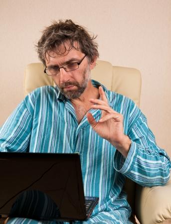 hombre maduro sentado en una silla con la computadora port�til