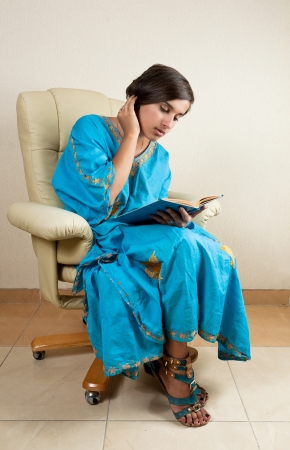 young girl sitting in chair reading book photo