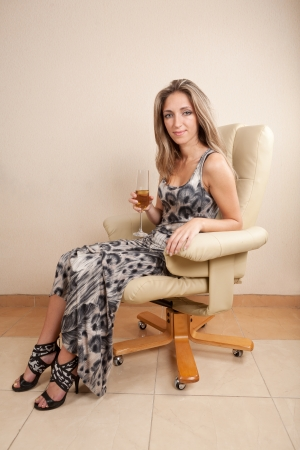 young woman sitting in chair drinking champagne Stock Photo - 15892364