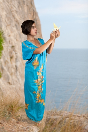 girl in blue indian dress with origami on seacoast photo