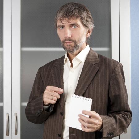 hombre en traje de negocios muestra el Bloc de notas en blanco