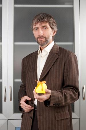 hombre en traje de negocios se extiende con caja de regalo Foto de archivo