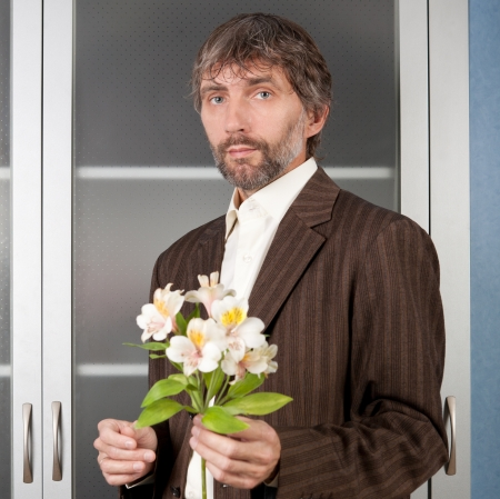 man in business suit stretches bouquet of flowers   Stock Photo - 16469819