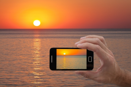 men hand holding smart phone with image from built-in camera of sunset