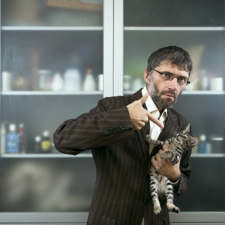 threatens: Male businessman holding his cat and threatens it
