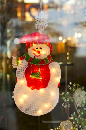 homey: snowman in holiday window xmas light background