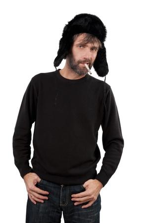 hombre adulto en orejeras sombrero sosteniendo cigarrillo aislado blanco Foto de archivo