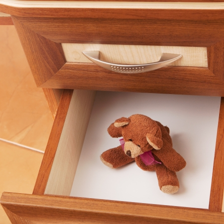 teddy bear in open desk drawer in a modern office photo