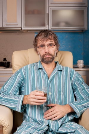 mature drunk man sitting in chair with glass photo