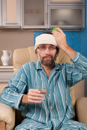 mature man sitting in chair with sad expression on his face holding glass of water